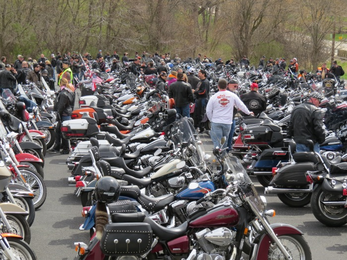 Harley riders waiting for the annual Blessing of the Bikes ride in the staging area at Uke's Harley Davidson in Kenosha, WI.  Every spring, hundreds of bikers join the ride to a church were they receive a blessing from a pastor for a safe riding season.