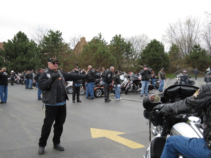 Bikers being directed into the church parking lot in Twin Lakes, WI. The Blessings of the Bikes ride was started after a biker was killed by a drunk driver. The widow got the event started and continued to ride every year until she suffered the same fate. The riders spoke of how they ride defensively – constantly on the lookout of their surroundings while on the road.