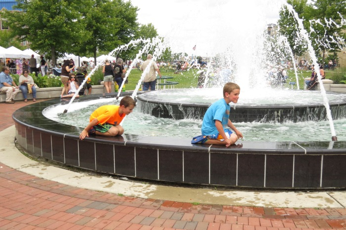 I hear laughter and my peripheral vision catches the movement of these two young gents playing on this fountain located outside the Kenosha Public Museum.  Summertime is fun time with water in any and all forms.