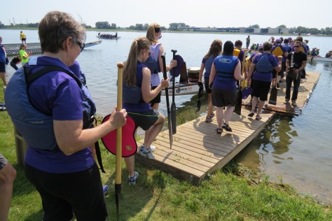 Teams wait to load their boats in the marshalling area. Once a boat becomes available they board and paddle to the starting line.