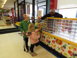 """Sam the """"Sample Man"""" handing samples of jelly beans to Isaiah, Elise and Everett."""